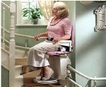 Happy lady on curved stairlift in Bristol
